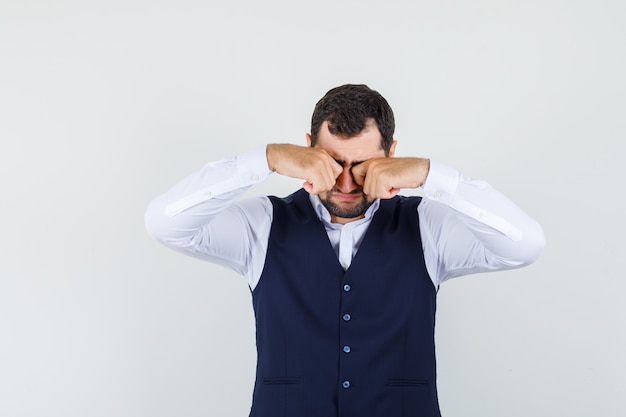 Jonge man in overhemd, vest dat zijn ogen wrijft en verdrietig kijkt