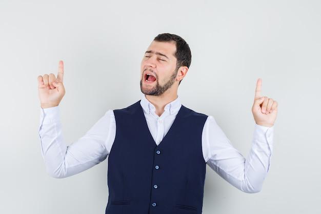 Jonge man in overhemd, vest die naar boven wijst en gelukkig kijkt