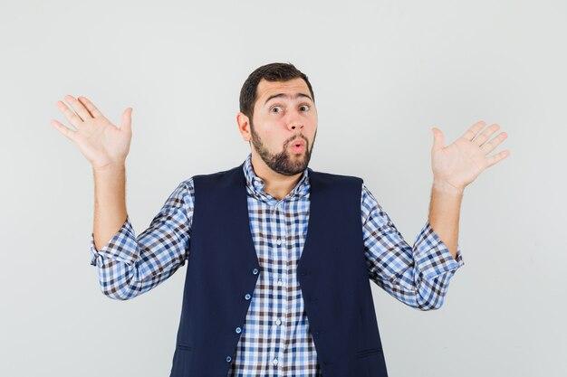 Jonge man in overhemd, vest overgave gebaar maken en op zoek bang, vooraanzicht.