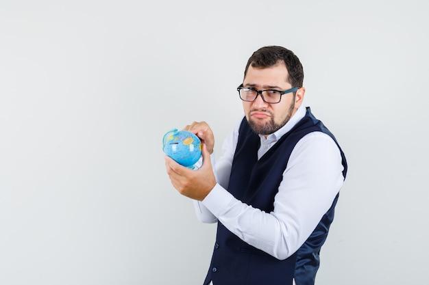 Jonge man in overhemd, vest wijst naar ergens op wereldbol en ziet er grappig uit