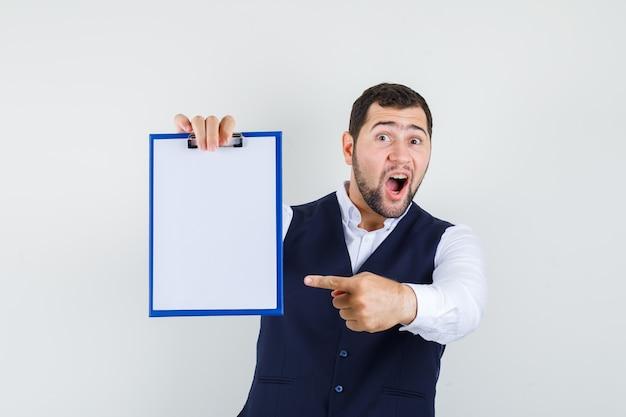 Jonge man in overhemd, vest wijzende vinger naar klembord en op zoek afgevraagd
