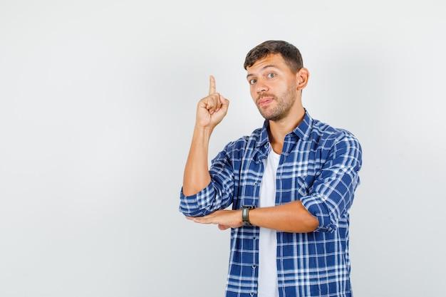 Jonge man in overhemd wijzende vinger en kijkt zelfverzekerd, vooraanzicht.