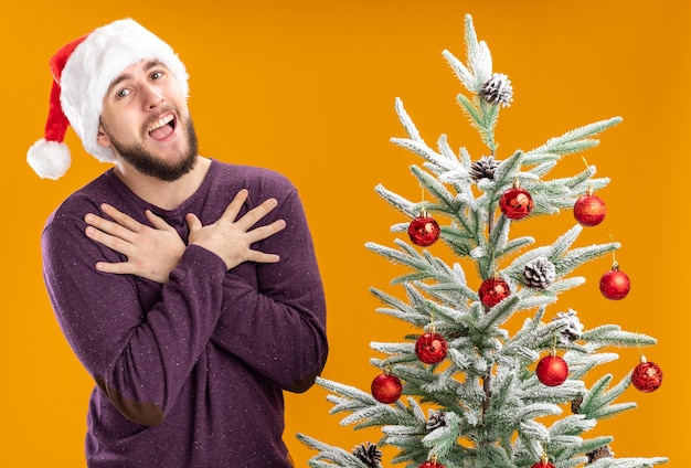 Jonge man in paarse trui en kerstmuts camera kijken met blij gezicht hand in hand op borst naast kerstboom over oranje achtergrond