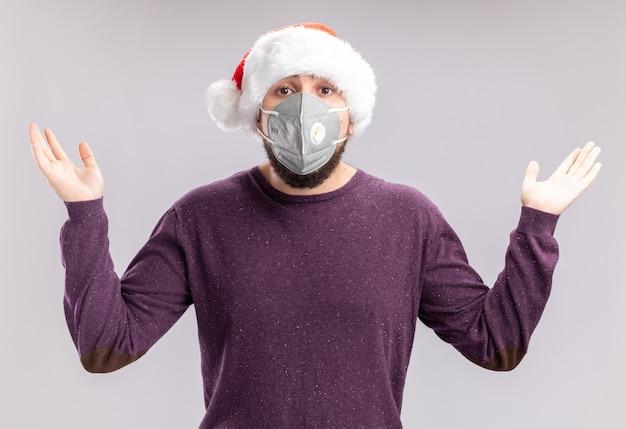 Jonge man in paarse trui en kerstmuts dragen gezicht beschermend masker camera kijken verward verspreiden handen naar de zijkanten zonder antwoord staande op witte achtergrond