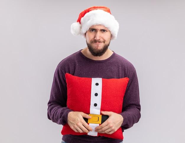 Jonge man in paarse trui en kerstmuts met een grappig kussen kijkend naar de camera die ontevreden is over het maken van een wrange mond die over een witte achtergrond staat