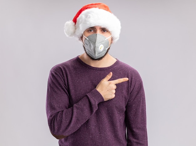 Jonge man in paarse trui en kerstmuts met gezichtsbeschermend kijkend naar camera met serieus gezicht wijzend met wijsvinger naar de zijkant over witte achtergrond
