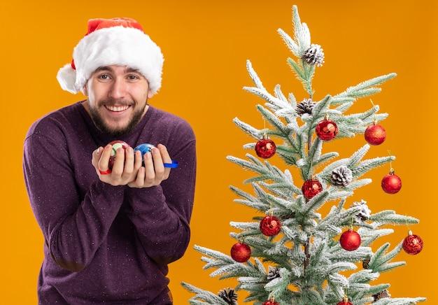 Jonge man in paarse trui en kerstmuts met kerstballen blij en opgewonden lachend staande naast kerstboom over oranje achtergrond