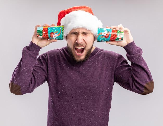 Jonge man in paarse trui en kerstmuts voor oren met kleurrijke papieren bekers schreeuwen met geïrriteerde uitdrukking staande over witte muur