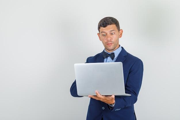 Jonge man in pak die op laptop werkt en druk kijkt