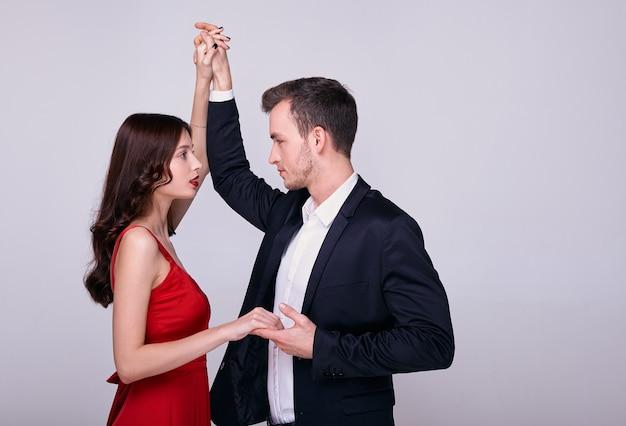 Jonge man in pak en vrouw in een rode jurk dansen geïsoleerd op een grijze achtergrond