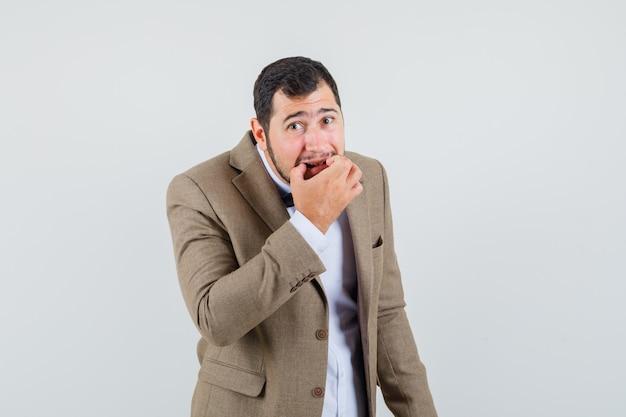 Jonge man in pak fluiten met vingers, vooraanzicht.
