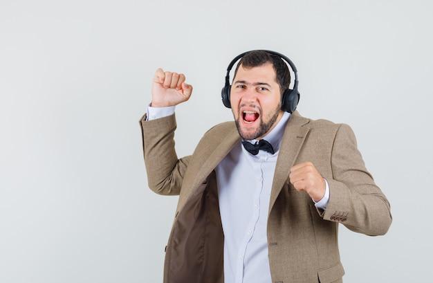 Jonge man in pak genieten van muziek met koptelefoon en op zoek dartel, vooraanzicht.