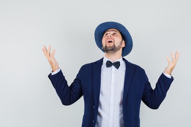 Jonge man in pak, hoed die handen opheft terwijl hij omhoog kijkt en dankbaar kijkt, vooraanzicht.