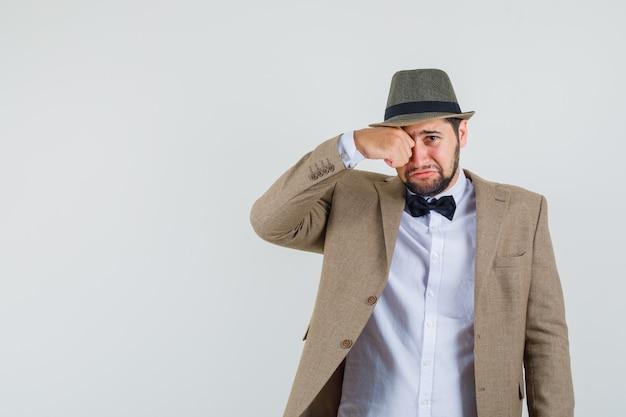Jonge man in pak, hoed wrijft in de ogen terwijl hij huilt als een kind en beledigd kijkt, vooraanzicht.
