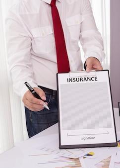 Jonge man in pak in zijn kantoor een verzekeringspolis tonen en wijzen met een pen