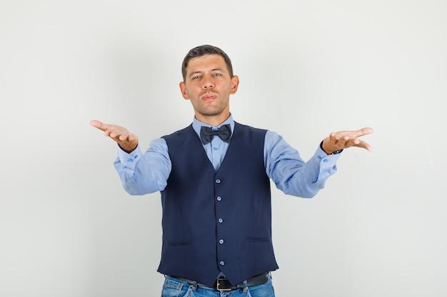 Jonge man in pak, jeans met open handpalmen