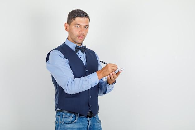 Jonge man in pak, jeans schrijven op mini-notebook