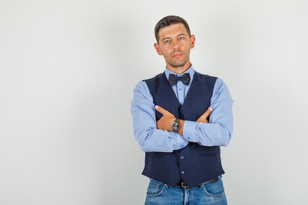 Jonge man in pak, jeans staan met gekruiste armen