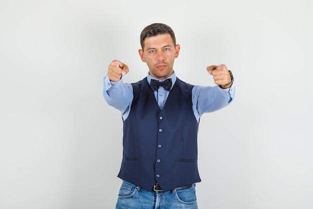 Jonge man in pak, jeans vingers naar de camera