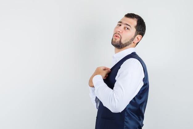 Jonge man in pak kraag van vest aanpassen en op zoek naar vertrouwen.