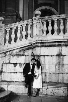 Jonge man in pak kussende vrouw die op muur leunt