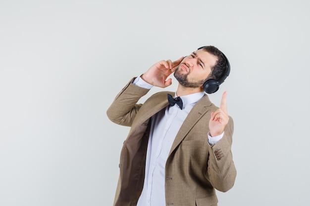Jonge man in pak luisteren met een koptelefoon en omhoog, vooraanzicht.