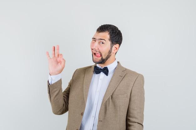 Jonge man in pak met ok gebaar en tong uitsteekt, vooraanzicht.