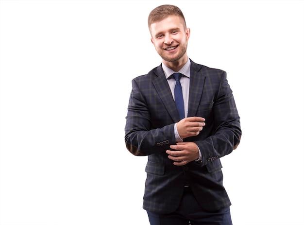Jonge man in pak past zijn manchetten aan en glimlacht