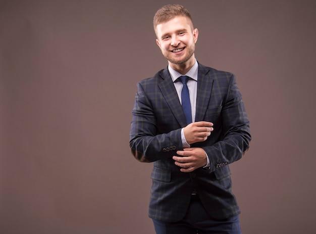 Jonge man in pak past zijn manchetten en glimlachen
