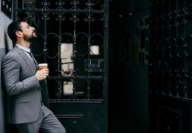 Jonge man in pak staat voor een oud gebouw en aarzelt om binnen te komen.