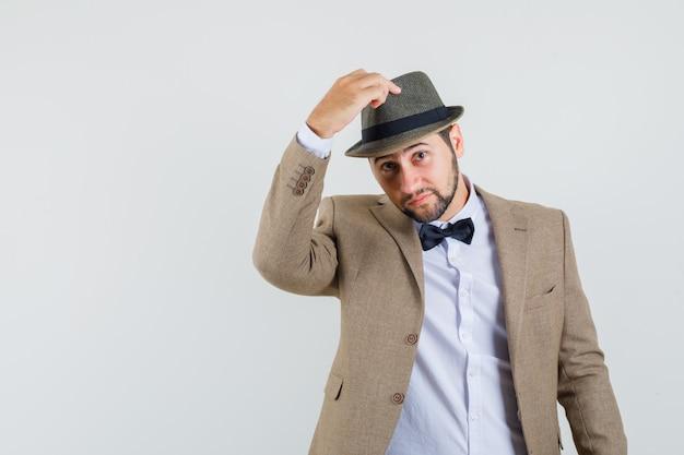 Jonge man in pak zijn hoed opstijgen en zacht, vooraanzicht kijken.