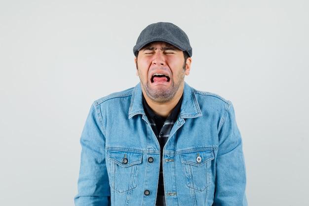 Jonge man in pet, t-shirt, jas huilen luid en kijkt beledigd