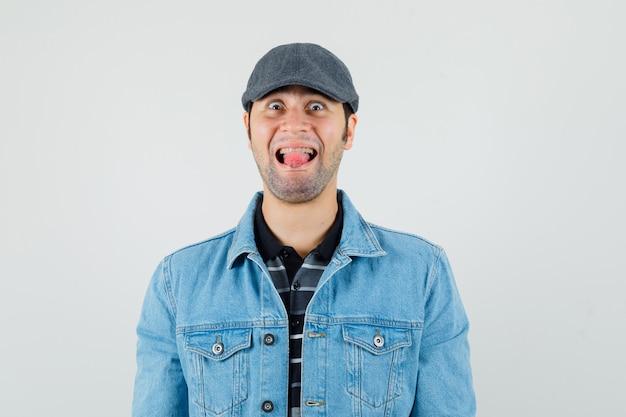 Jonge man in pet, t-shirt, jasje tong uitsteekt en op zoek grappig