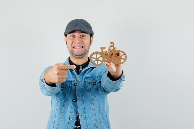 Jonge man in pet, t-shirt, jasje wijzend op houten speelgoedfiets en er vrolijk uit
