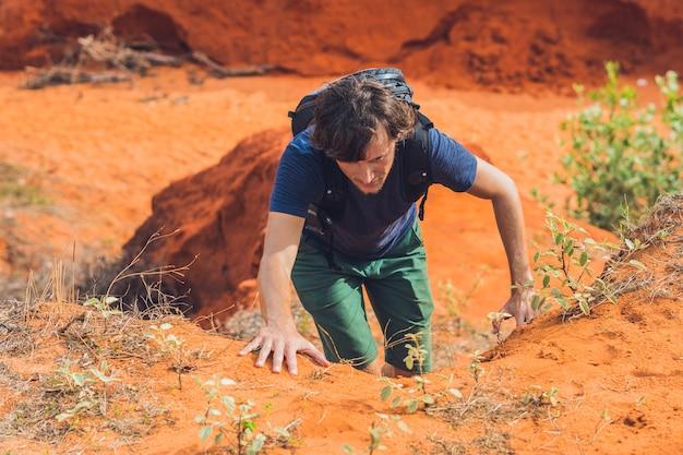 Jonge man in rode canyon in de buurt van mui ne, zuid-vietnam