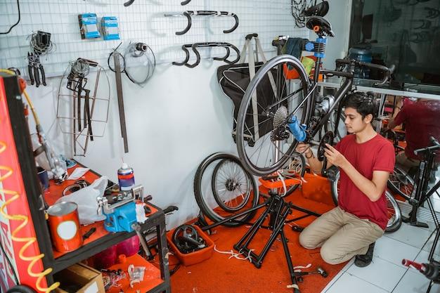 Jonge man in rode kleren aan het werk aan het monteren van fietscrankstel met gereedschap