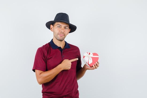 Jonge man in rood shirt, zwarte hoed wijst naar cadeau en kijkt blij, vooraanzicht.