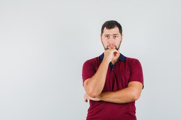Jonge man in rood t-shirt kijkt uit en kijkt geconcentreerd, vooraanzicht.