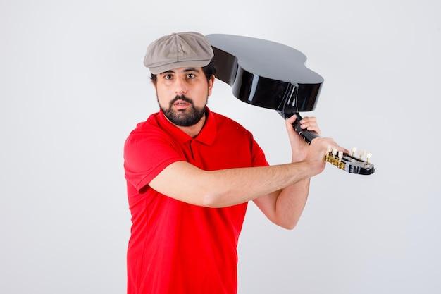 Jonge man in rood t-shirt, pet verhogen gitaar met agressieve manier, vooraanzicht.