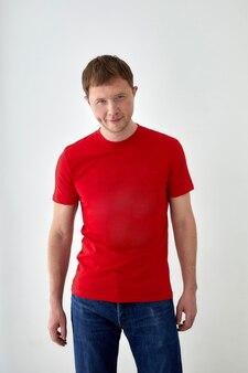 Jonge man in rood t-shirt tegen witte achtergrond