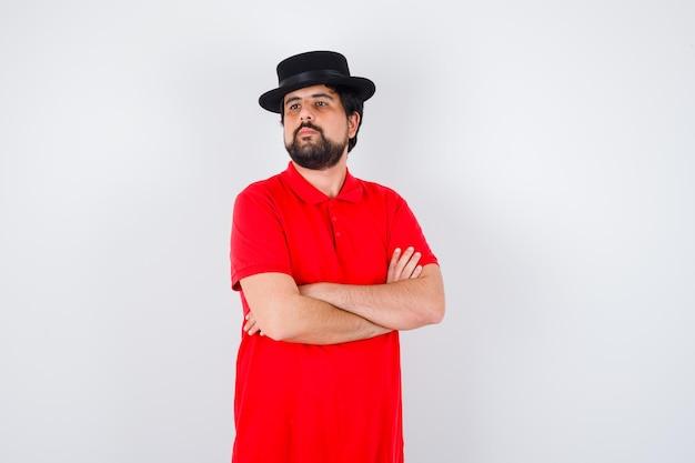 Jonge man in rood t-shirt, zwarte hoed met gekruiste armen en zelfverzekerd, vooraanzicht.