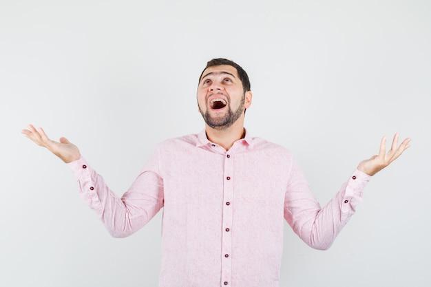 Jonge man in roze shirt handen opheffen terwijl opzoeken en gelukkig kijken
