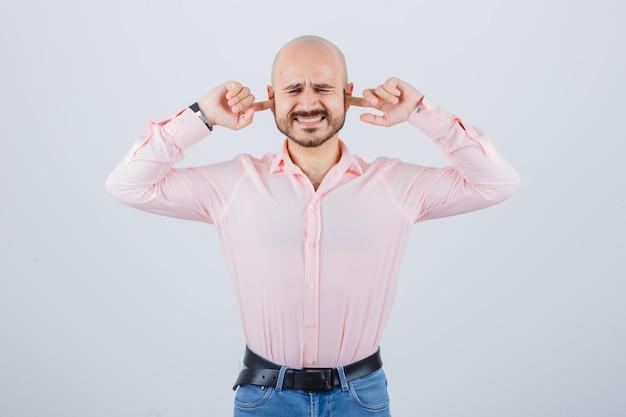 Jonge man in roze shirt, jeans die oren inplugt met vingers, vooraanzicht.
