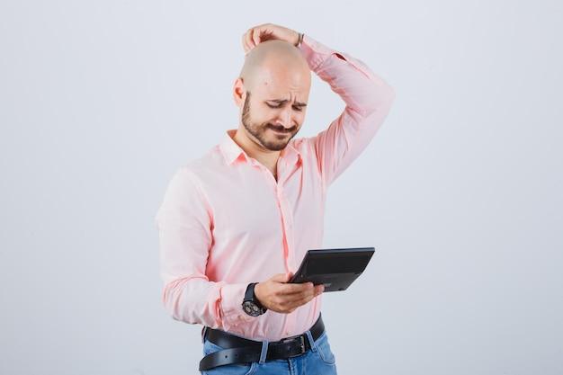 Jonge man in roze shirt, jeans die zijn hoofd krabt terwijl hij naar de rekenmachine kijkt en peinzend kijkt, vooraanzicht.