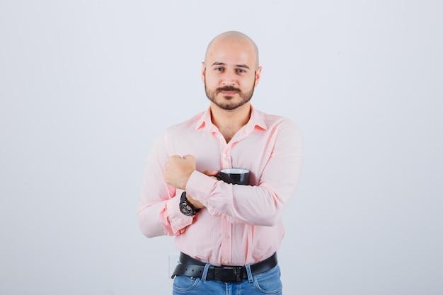 Jonge man in roze shirt, jeans knuffelen zijn kopje, vooraanzicht.