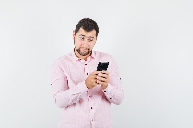 Jonge man in roze shirt met behulp van mobiele telefoon en vraagt zich af