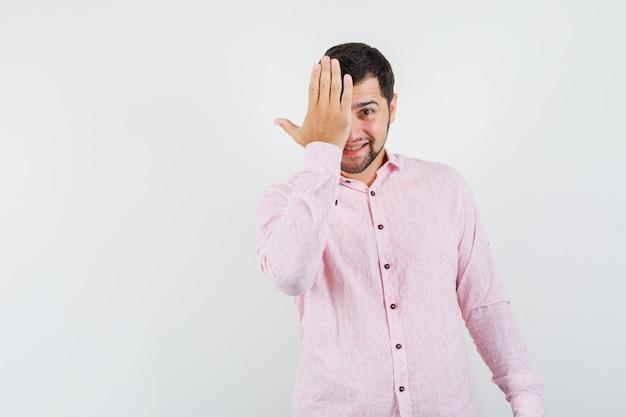 Jonge man in roze shirt met hand op één oog en verlegen kijkt