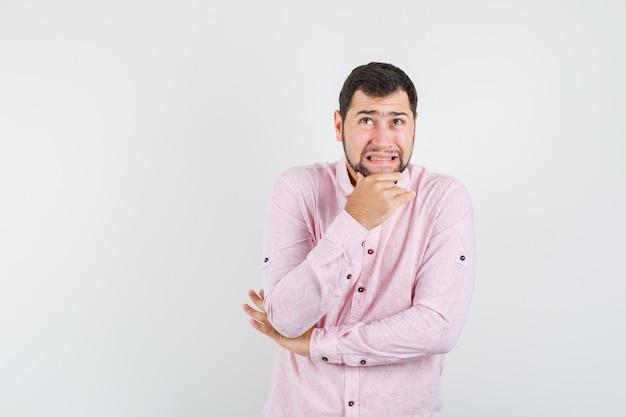 Jonge man in roze shirt met kin terwijl hij omhoog kijkt en onrustig kijkt