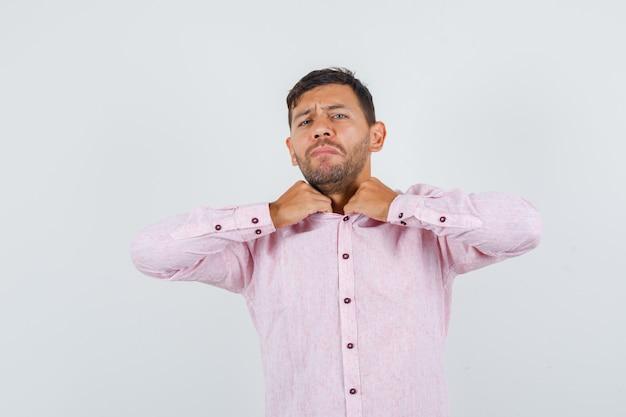 Jonge man in roze shirt ongemakkelijk gevoel vanwege strakke kraag, vooraanzicht.