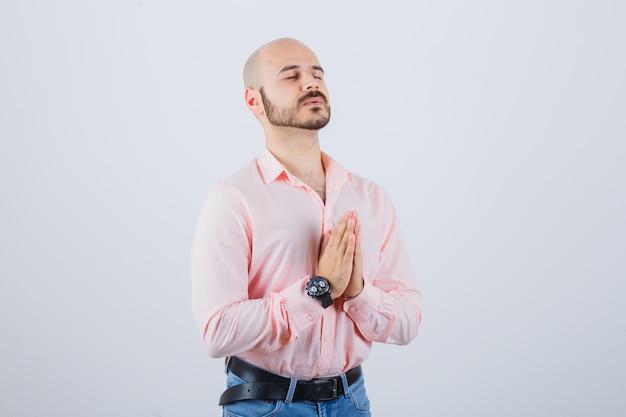 Jonge man in roze shirt, spijkerbroek bidden en op zoek naar wens, vooraanzicht.